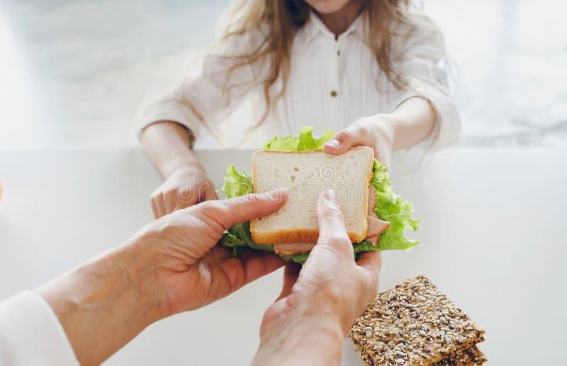 A mãe dá o fim do sanduíche da filha acima do café da manhã saudável fotos de stock