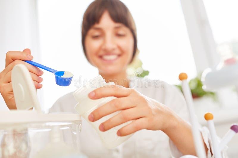A mãe dá o probiotics ao comida para bebê imagem de stock royalty free