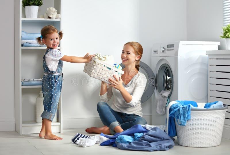 Mãe da família e ajudante pequeno da criança na lavandaria perto do washi imagem de stock royalty free