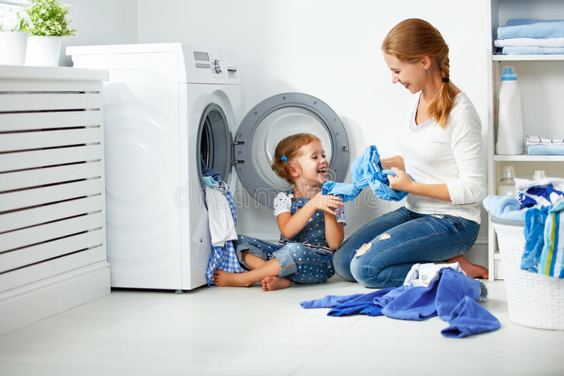 Mãe da família e ajudante pequeno da menina da criança na lavandaria perto da máquina de lavar imagem de stock