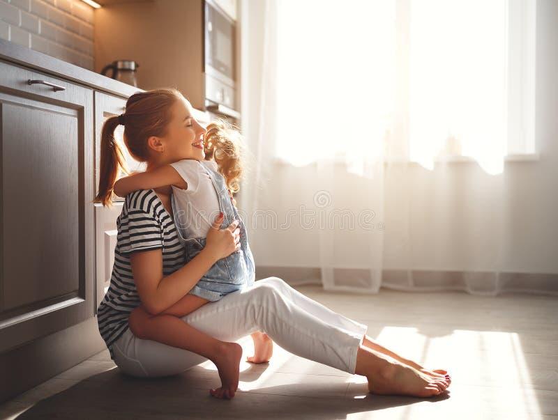 Mãe da família e filha da criança que abraça na cozinha no assoalho fotografia de stock royalty free