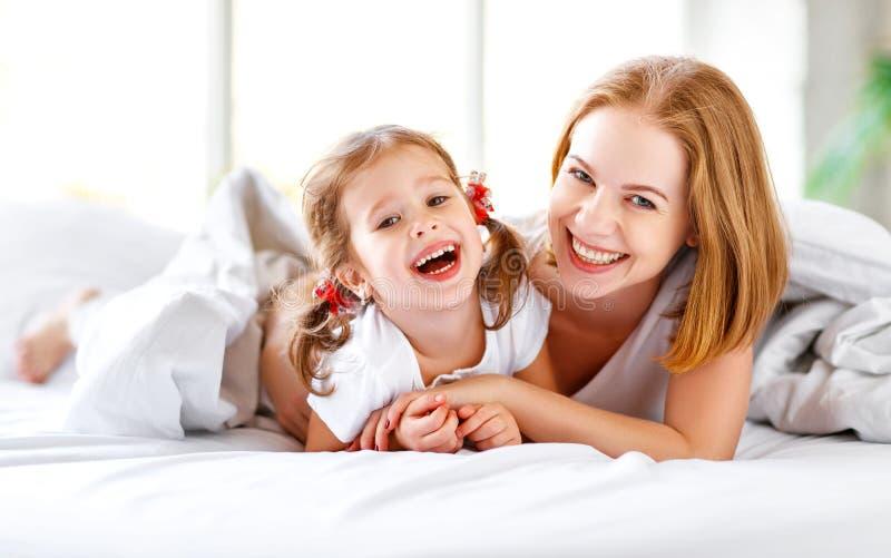 A mãe da família e a filha felizes da criança riem na cama fotos de stock