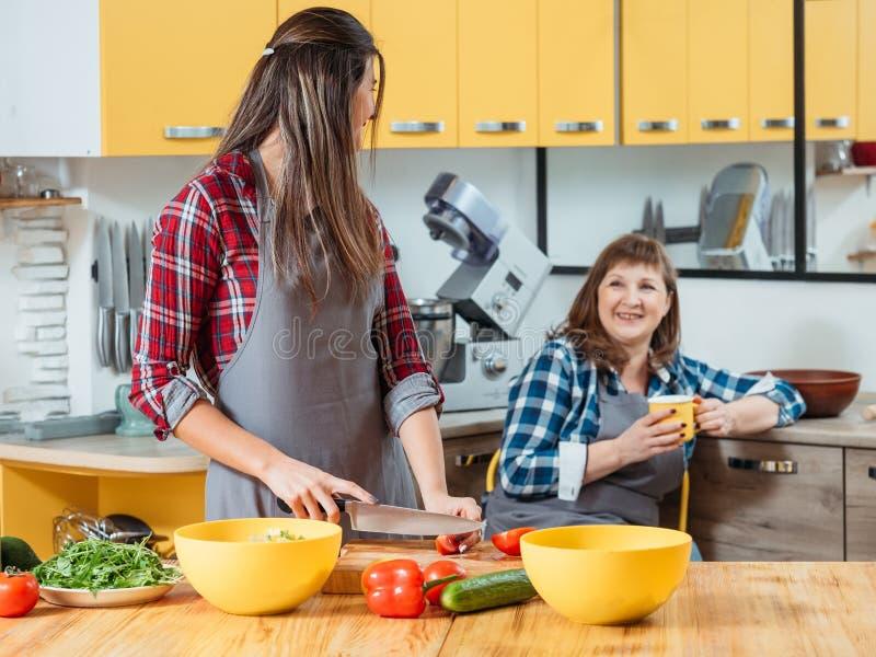 M?e da filha que cozinha o tempo do ch? da salada junto imagem de stock