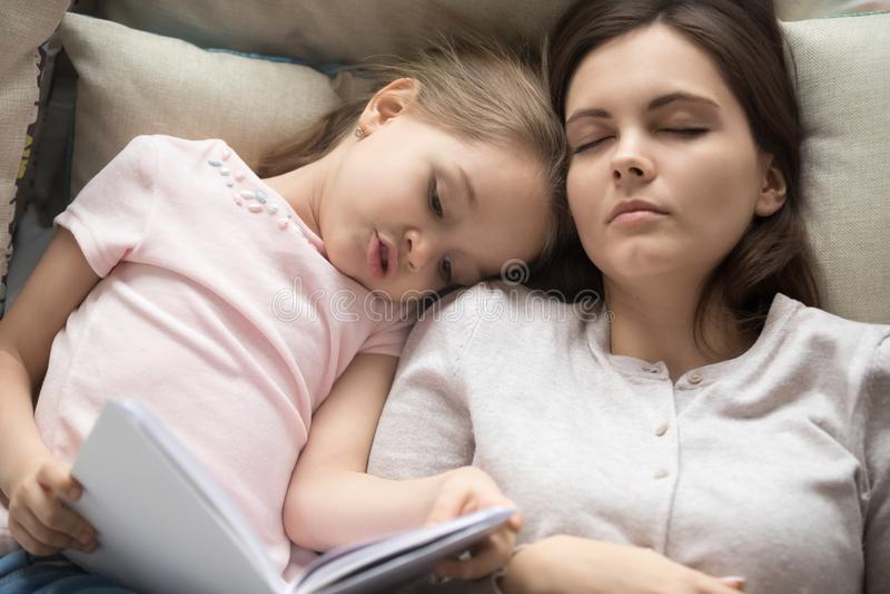 A mãe da vista superior cair adormecido quando seu livro de leitura da filha fotos de stock royalty free