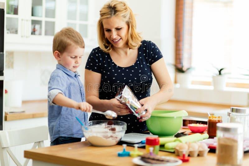 Mãe de ajuda da criança bonito esperta na cozinha fotografia de stock royalty free