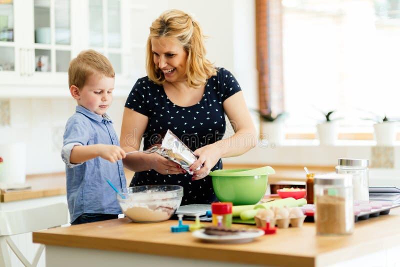 A mãe de ajuda da criança coze cookies imagem de stock royalty free