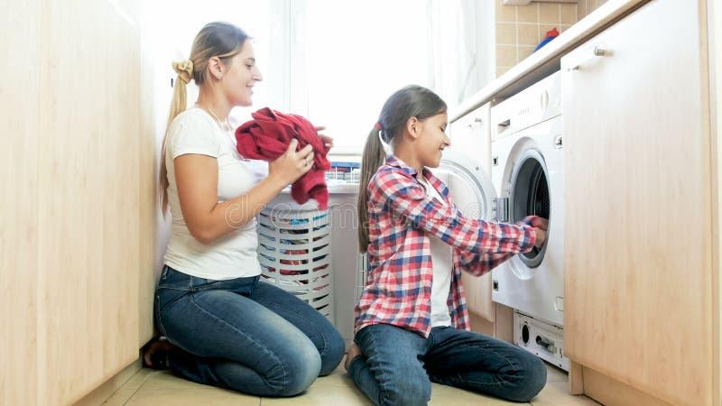 Mãe de ajuda de sorriso bonita do adolescente na lavandaria foto de stock
