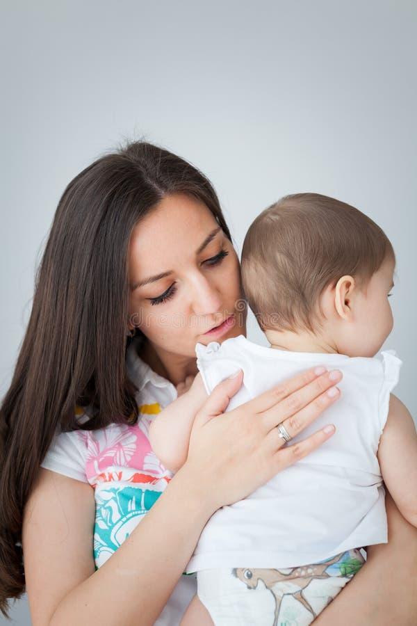 A mãe de amor está acalmando seu bebê batendo e fazendo massagens sua parte traseira fotografia de stock royalty free
