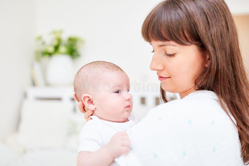 A mãe de amor guarda seu bebê em seus braços imagem de stock royalty free