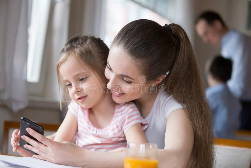 Mãe de amor que senta-se com a filha que usa o telefone celular fotografia de stock royalty free