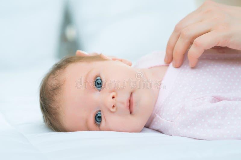 Mãe de cuidados que põe sua criança pequena na cama foto de stock