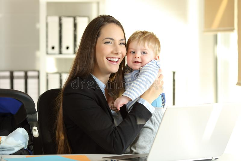 Mãe de funcionamento feliz que levanta com seu bebê no escritório fotografia de stock royalty free