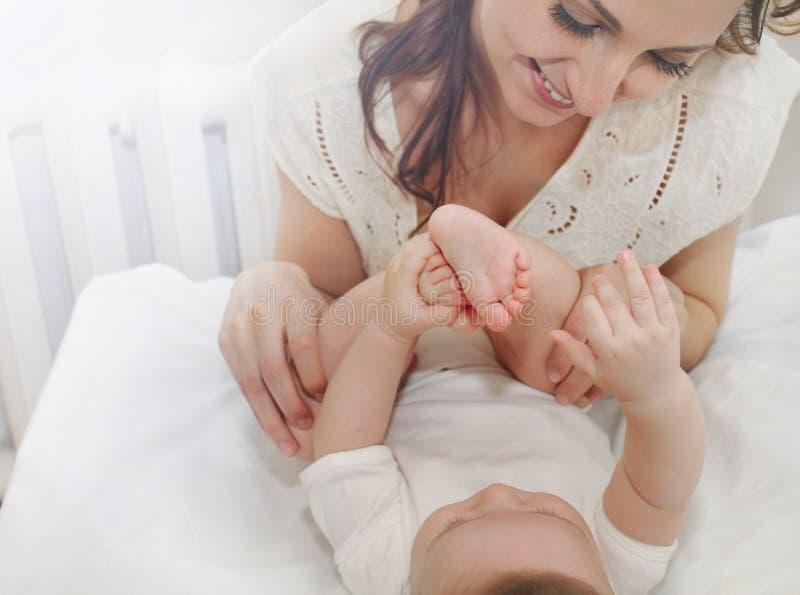 A mãe de inquietação feliz admira os dedos pequenos de seu bebê bonito imagem de stock