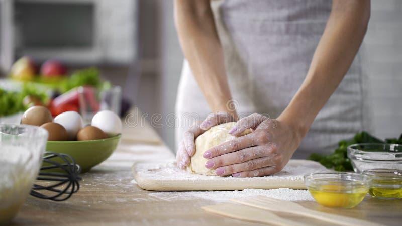 Mãe de inquietação que amassa a massa na cozinha, mulher que faz bolos, parte-vista imagens de stock royalty free