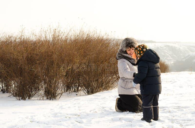 Mãe de inquietação que verifica sua roupa dos filhos no inverno foto de stock royalty free