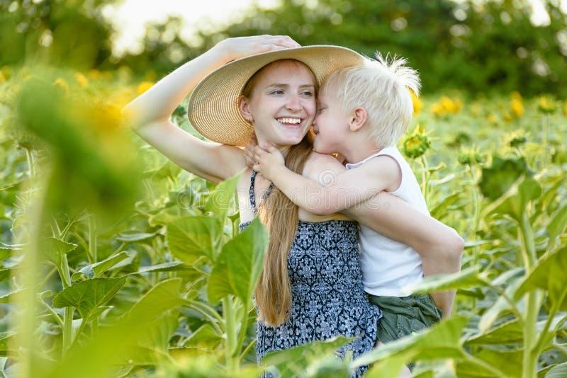 A mãe de riso feliz que dá o passeio do reboque do filho da criança no fundo de girassóis de florescência verdes coloca foto de stock royalty free