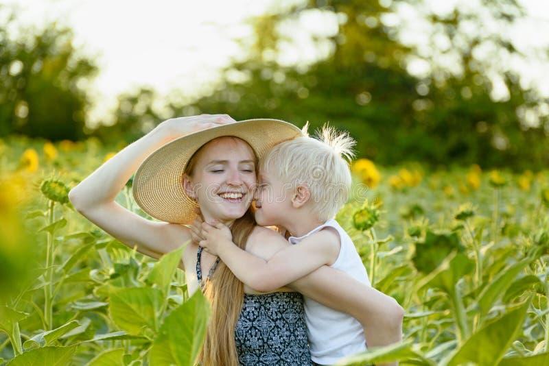 A mãe de riso feliz que dá o passeio do reboque do filho da criança no fundo de girassóis de florescência verdes coloca fotografia de stock