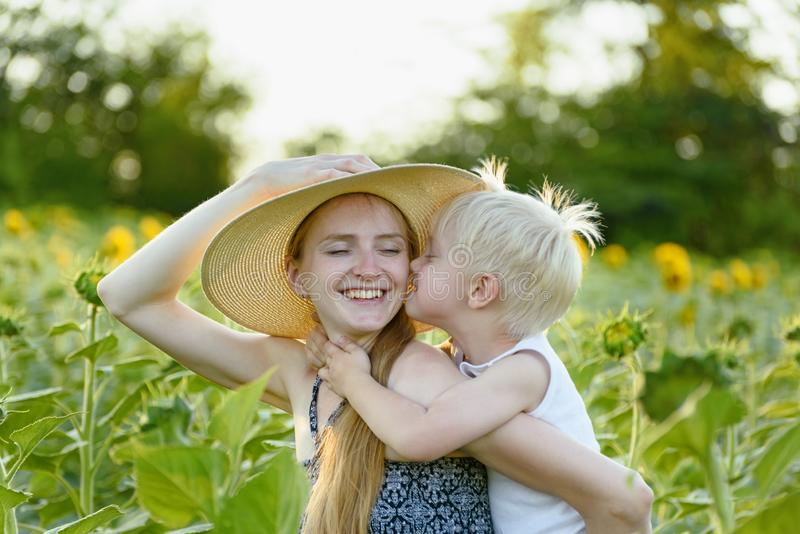 A mãe de riso feliz que dá o passeio do reboque do filho da criança no fundo de girassóis de florescência verdes coloca imagens de stock royalty free
