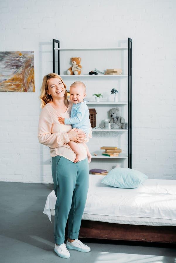 mãe de riso que leva sua criança pequena fotografia de stock