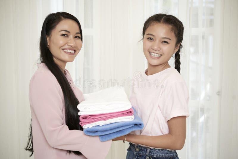 Mãe de sorriso com a filha que faz trabalhos domésticos fotos de stock
