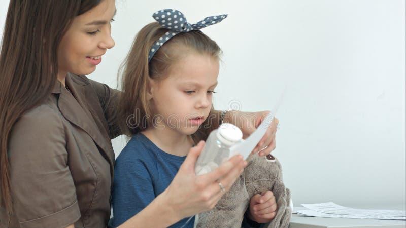 Mãe de sorriso com a menina bonito que guarda comprimidos e o formulário médico fotos de stock royalty free