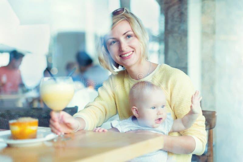 Mãe de sorriso com o bebê que olha através da janela fotos de stock