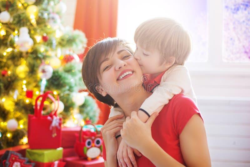 Mãe de sorriso com seu filho pequeno na sala de visitas decorada para o Natal imagens de stock royalty free