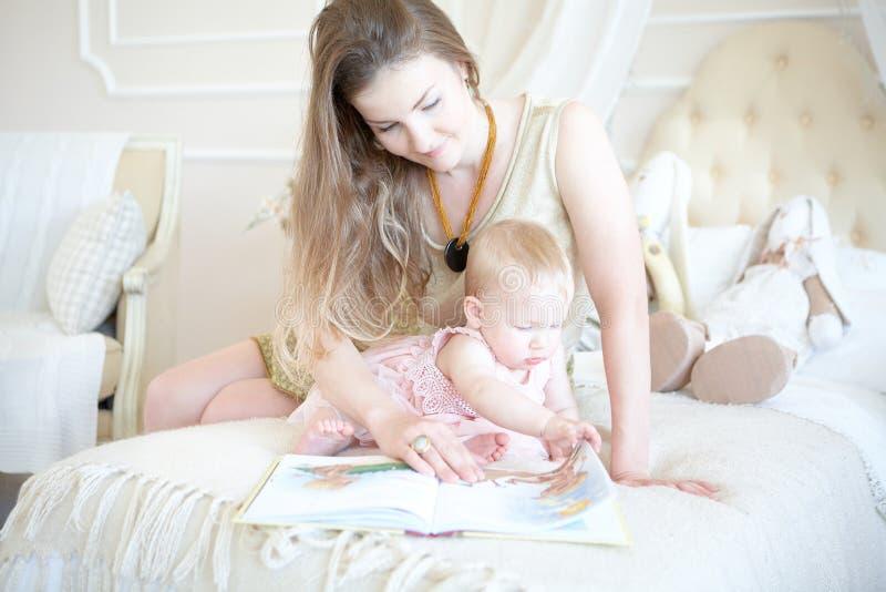 A mãe de sorriso e sua filha pequena na cama leram o livro imagens de stock