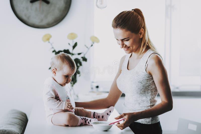 A mãe de sorriso feliz alimenta a criança adorável em casa fotografia de stock