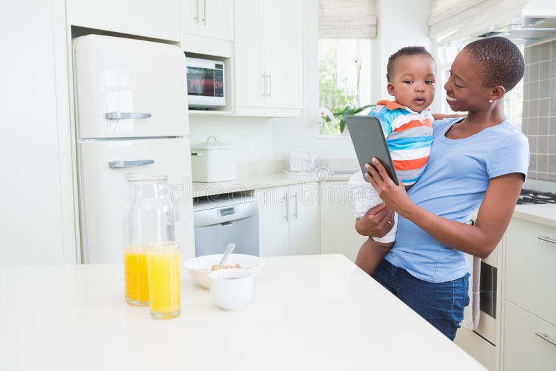 Mãe de sorriso feliz com o o seu babyboy foto de stock royalty free