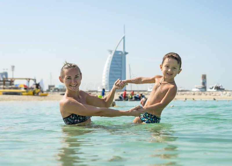 Mãe de sorriso feliz e seu filho que jogam e que correm na praia Conceito da família amigável imagem de stock royalty free