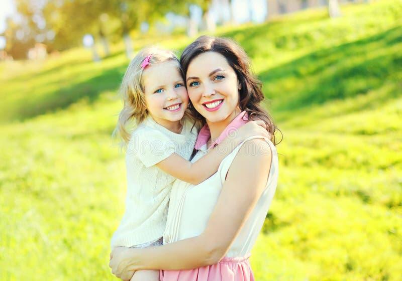 Download Mãe De Sorriso Feliz Que Abraça A Filha Da Criança No Verão Imagem de Stock - Imagem de feliz, outdoors: 65576093