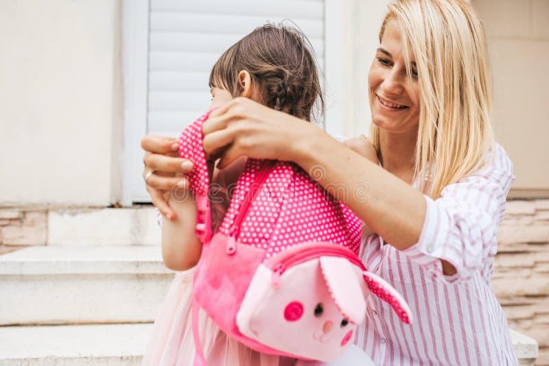 Mãe de sorriso feliz que prepara a trouxa para pôr sobre a trouxa a sua filha da criança a ir ao jardim de infância sobre exterio imagem de stock