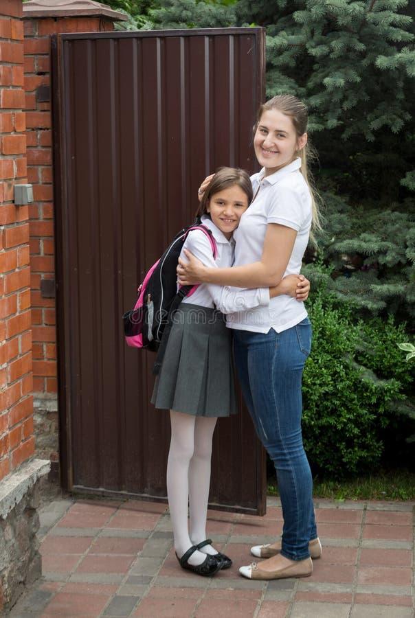 Mãe de sorriso nova que vê fora de sua filha à escola imagens de stock