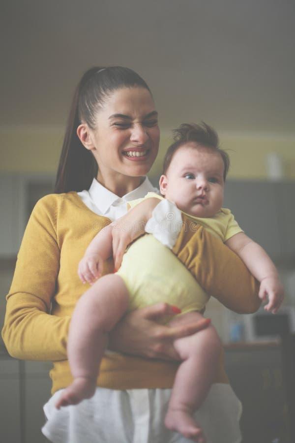 Mãe de sorriso que guarda seu bebê nos braços imagens de stock royalty free