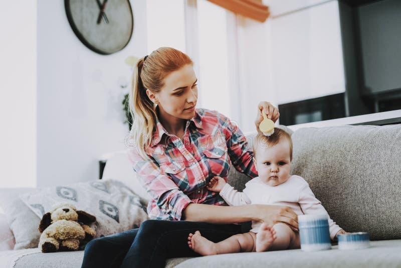 Mãe de sorriso que penteia o cabelo do bebê bonito dentro fotos de stock
