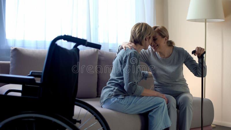 Mãe deficiente que senta-se no sofá e que fala à filha, apoio da família, cuidado imagem de stock