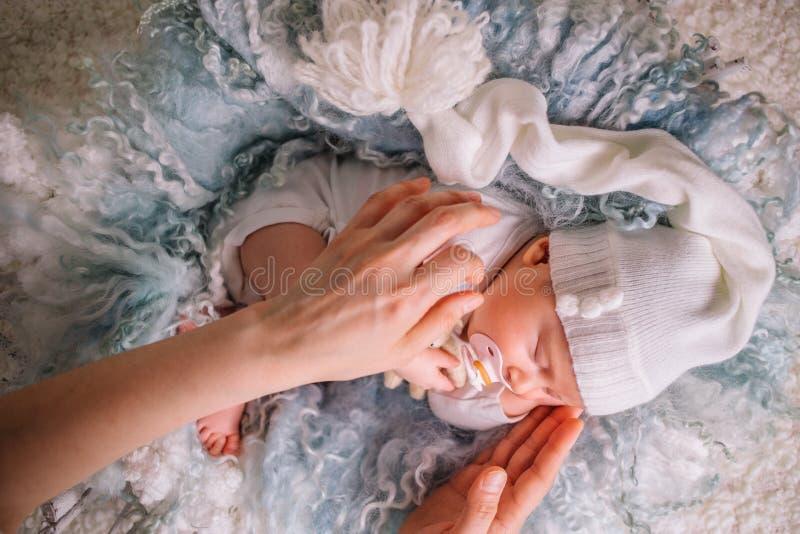 Mãe delicada das mãos a criança cai adormecido fotografia de stock