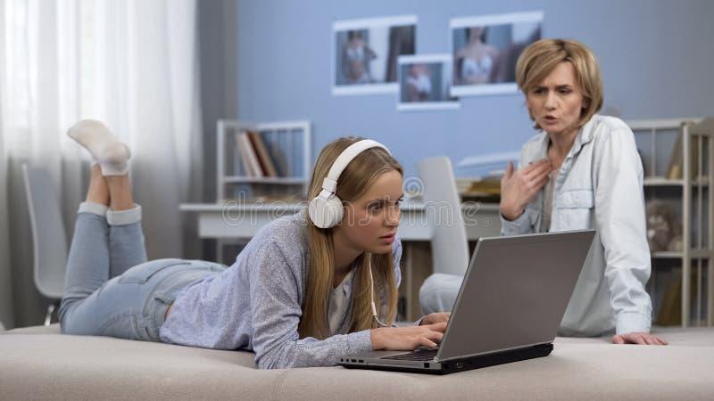 A mãe discute a filha, adolescente incomodado passa demasiada hora em meios sociais fotos de stock