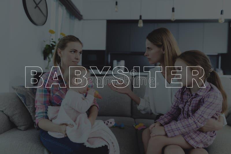 A mãe discute uma baby-sitter em casa foto de stock