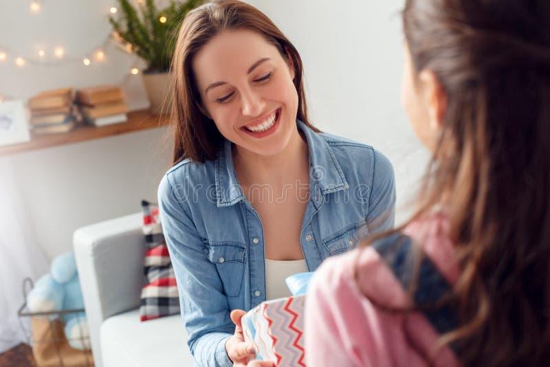 Mãe do assento do dia de mãe da mãe e da filha em casa que guarda a caixa atual do close-up alegre da filha fotos de stock royalty free