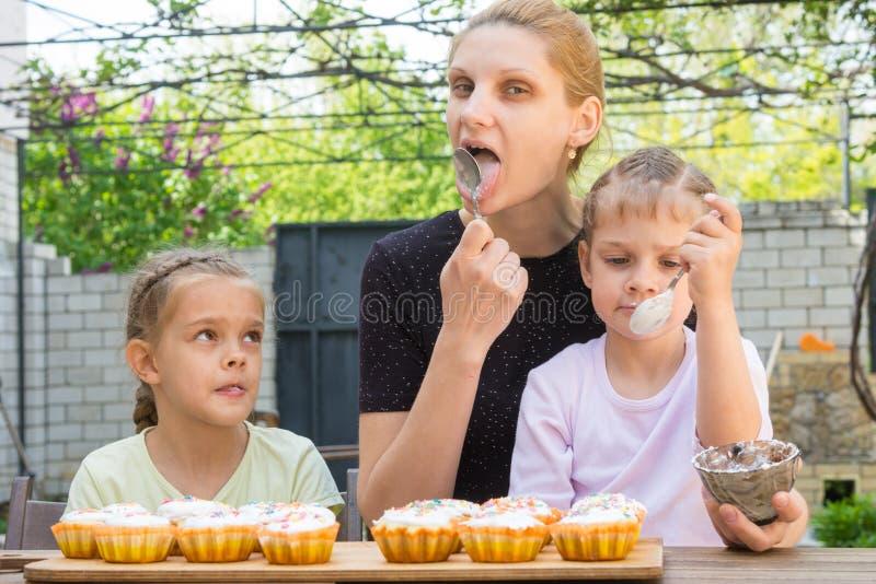 A mãe, duas filhas lambe colheres com crosta de gelo dos confeitos para queques da Páscoa fotos de stock royalty free