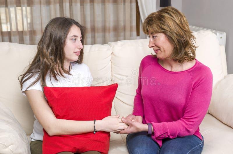 Mãe e adolescente em processo de fazer a paz em casa imagens de stock royalty free