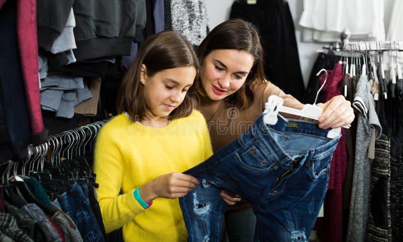 Mãe e adolescente que compram calças de brim na moda fotografia de stock