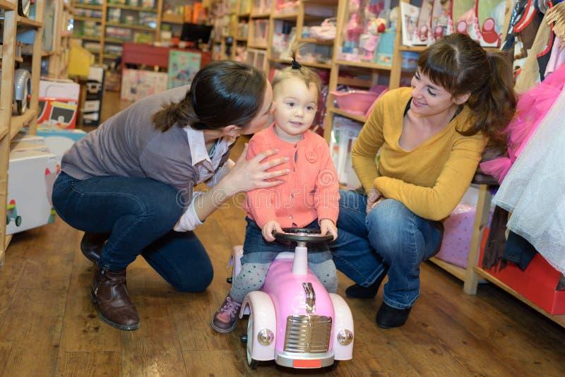 Mãe e amigo que ajudam para fora a filha com caminhão do brinquedo fotos de stock