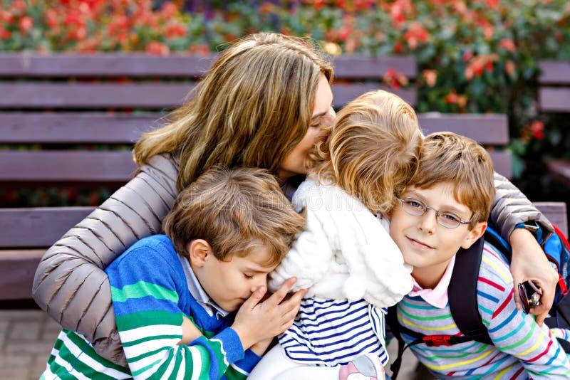Mãe e aperto de três crianças Assento feliz da família exterior: mulher e duas crianças pequenas do menino das crianças do irmão  imagens de stock