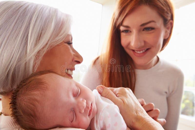 Mãe e avó com a filha recém-nascida de sono do bebê imagem de stock royalty free
