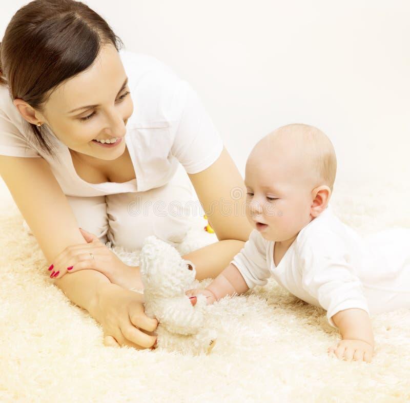 Mãe e bebê, criança que levanta a cabeça, família que joga Toy Bear imagem de stock royalty free