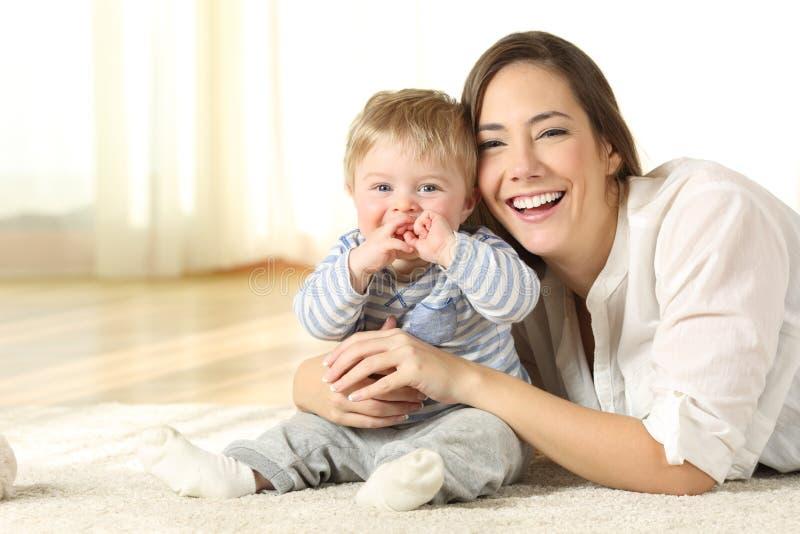 Mãe e bebê do smiley que olham o em casa foto de stock royalty free
