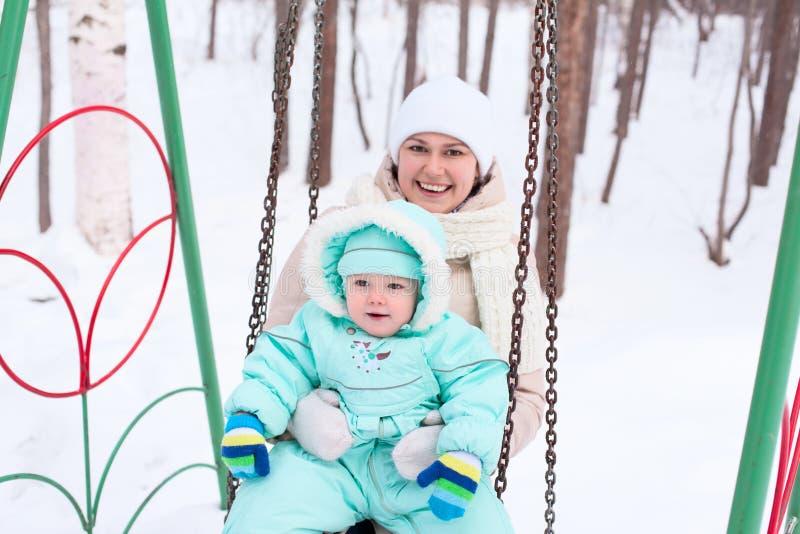 Mãe e bebê felizes da família no parque no inverno imagem de stock